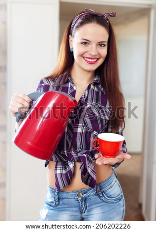 Portrait of happy pretty housewife with red tea kettle and cup at home - stock photo