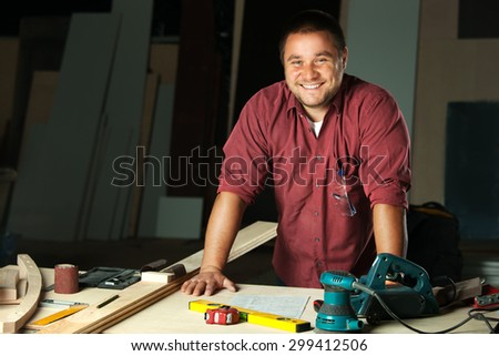 Portrait of happy professional carpenter at his work place. - stock photo