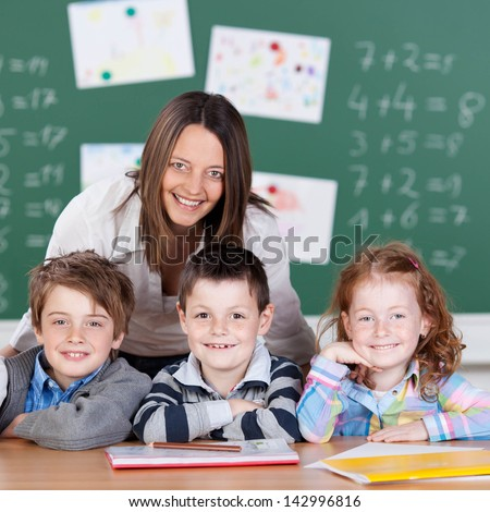 Portrait of happy pupils and teacher studying inside the classroom - stock photo