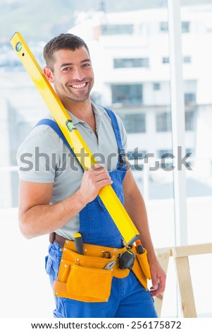 Portrait of happy repairman in overalls holding spirit level in bright office - stock photo