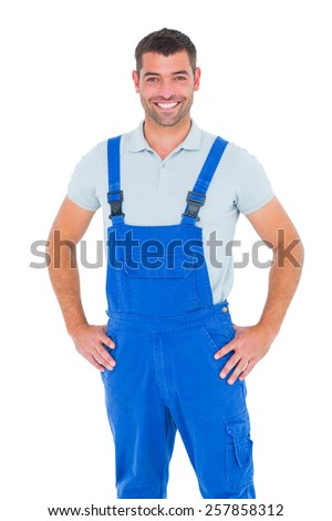 Portrait of happy repairman in overalls with hands on hip over white backgound - stock photo