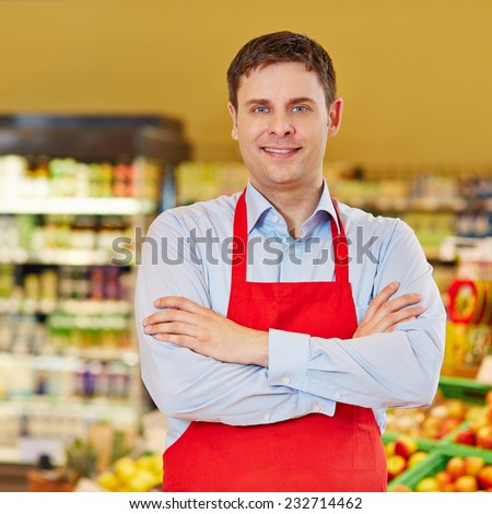 Portrait of happy retail salesman in a supermarket - stock photo