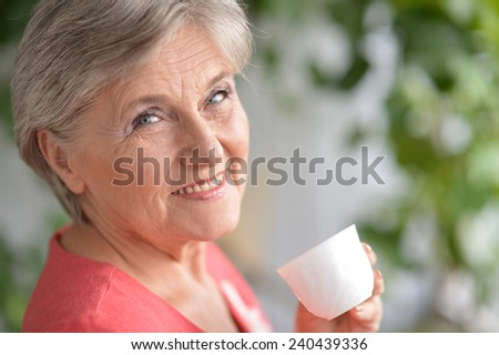 Portrait of happy retired woman drinking tea on blue background - stock photo