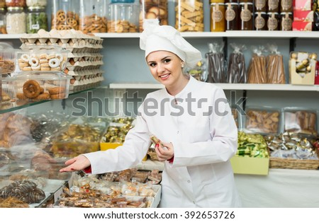Portrait of happy russian young chef at confectionery display with pastry - stock photo