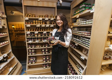 Portrait of happy saleswoman showing product in grocery store
