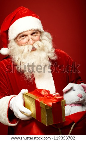 Portrait of happy Santa Claus giving Christmas present - stock photo