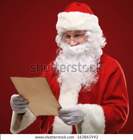 Portrait of happy Santa Claus holding Christmas letter and looking at camera
