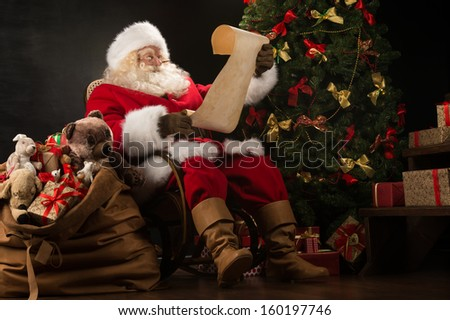 Portrait of happy Santa Claus sitting at his room at home near Christmas tree and big sack and reading Christmas letter or wish list - stock photo