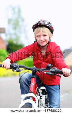 Portrait of happy school boy in safety helmet riding his bike on the street in a countryside