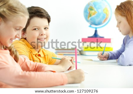 Portrait of happy schoolboy looking at camera between two girls - stock photo
