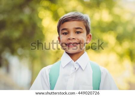 Portrait of happy schoolboy standing in campus at school - stock photo