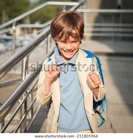 Portrait of happy schoolboy with  backpack, outdoor - stock photo