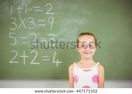 Portrait of happy schoolgirl smiling in classroom at school - stock photo