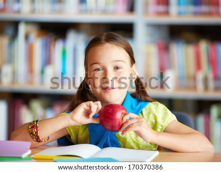 Portrait of happy schoolgirl with apple looking at camera in library - stock photo