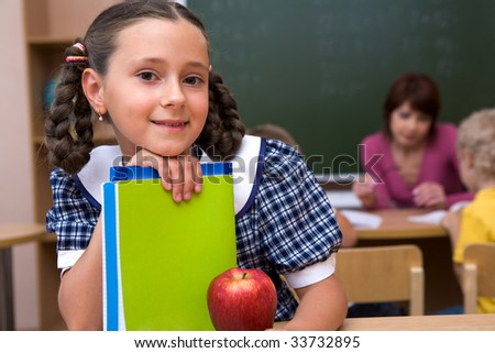 Portrait of happy schoolgirl with copybooks looking at camera