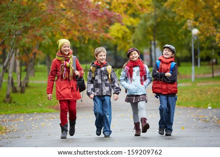 Portrait of happy schoolkids going to school - stock photo