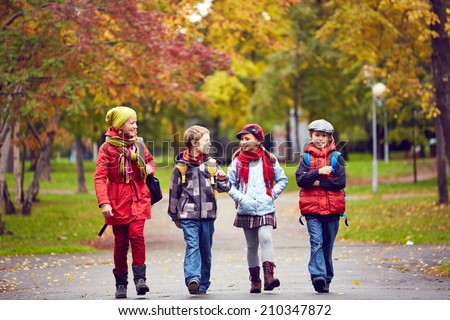 Portrait of happy schoolkids talking while going to school - stock photo