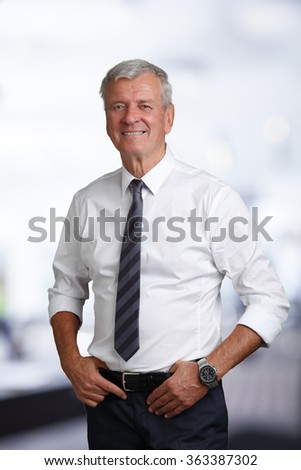 Portrait of happy senior businessman looking at camera and smiling while standing at office after business meeting.