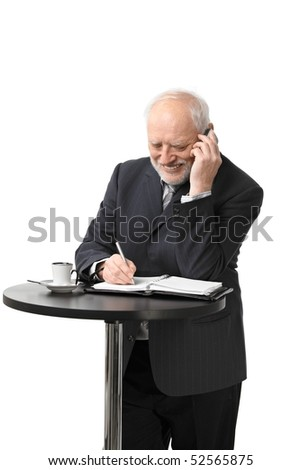 Portrait of happy senior businessman standing at coffee table talking on mobile phone, isolated on white.