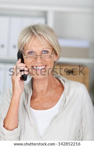 Portrait of happy senior businesswoman conversing on cordless phone at office - stock photo