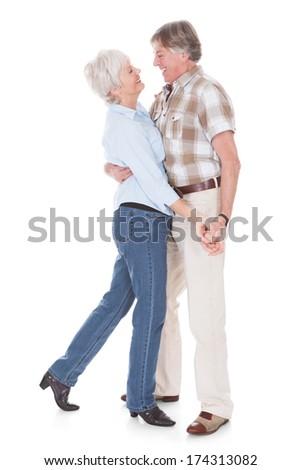 Portrait Of Happy Senior Couple Dancing Over White Background. - stock photo