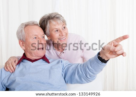 Portrait Of Happy Senior Couple Gesturing And Sitting On Couch - stock photo