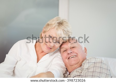 Portrait of happy senior couple in bed at home - stock photo