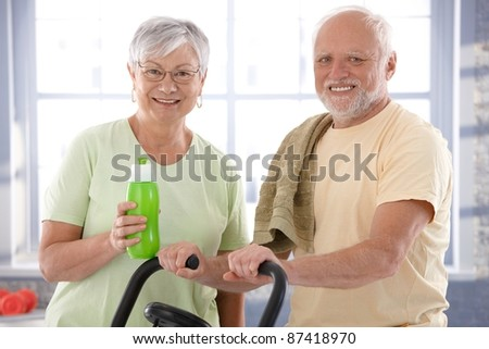 Portrait of happy senior couple in the gym, looking at camera.? - stock photo