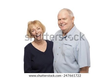 Portrait of happy senior couple laughing against white background - stock photo