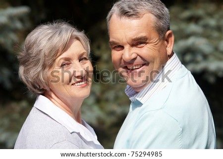 Portrait of happy senior couple looking at camera on sunny day - stock photo