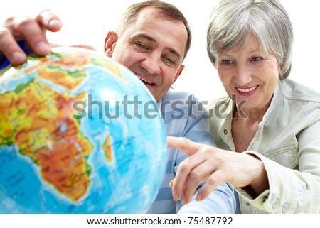 Portrait of happy senior couple looking at globe - stock photo
