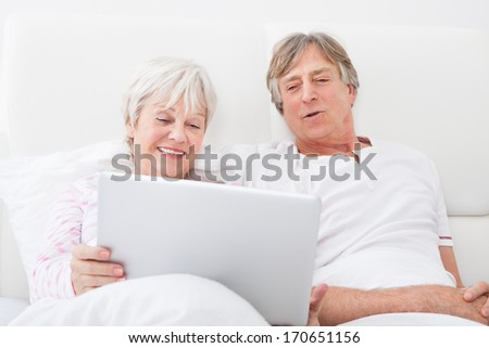 Portrait Of Happy Senior Couple Lying On Bed Looking At Laptop - stock photo