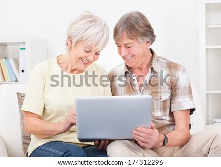 Portrait Of Happy Senior Couple Sitting On Couch Using Laptop - stock photo