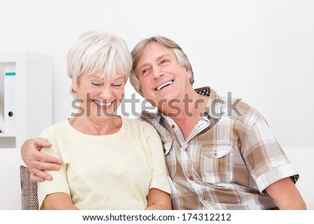 Portrait Of Happy Senior Couple Sitting Together Side By Side - stock photo