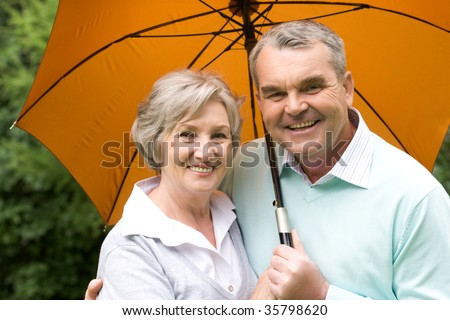 Portrait of happy senior couple under umbrella during rain - stock photo