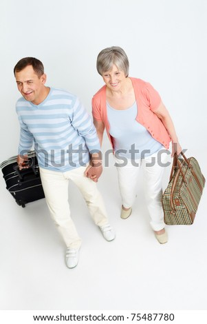 Portrait of happy senior couple with baggage - stock photo