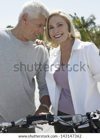 Portrait of happy senior couple with bicycles on beach - stock photo
