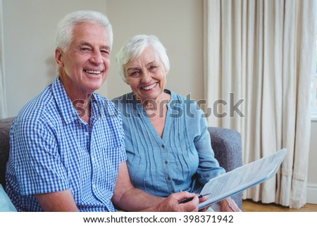 Portrait of happy senior couple with bills while sitting on sofa at home - stock photo