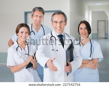 Portrait of happy senior doctor offering handshake while standing with team in hospital - stock photo