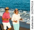 Portrait of happy senior fitness women jogging on beach. - stock photo