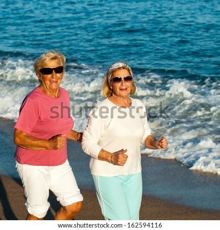 Portrait of happy senior fitness women jogging on beach. - stock photo