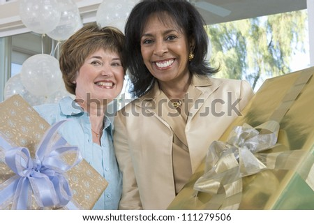 Portrait of happy senior friends holding gift at party - stock photo