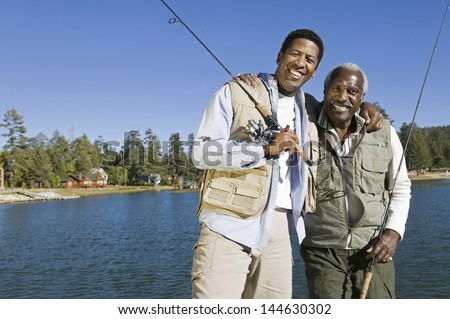 Portrait of happy senior man and adult son holding fishing rods by lake - stock photo