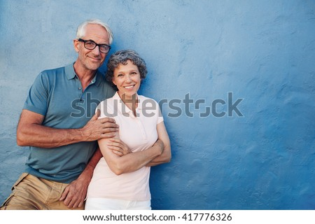 Portrait of happy senior man and woman together against blue background. Middle aged couple looking at camera and smiling with copy space on blue wall. - stock photo