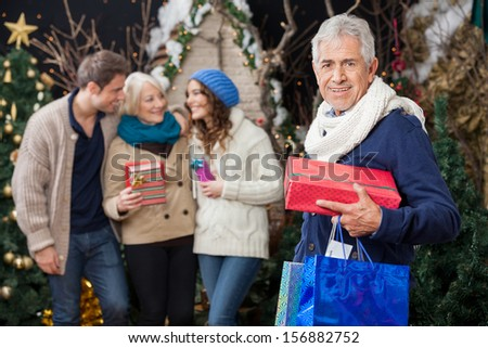 Portrait of happy senior man holding Christmas presents with family standing in background at store - stock photo