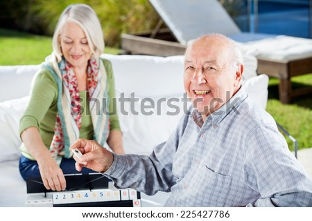 Portrait of happy senior man playing rummy with woman at nursing home - stock photo