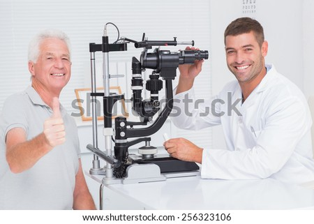 Portrait of happy senior man showing thumbs up while sitting with optician in clinic - stock photo