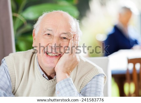 Portrait of happy senior man sitting at nursing home with grandson in background - stock photo