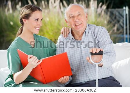 Portrait of happy senior man sitting by female nurse holding book at nursing home - stock photo