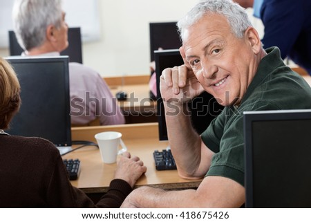 Portrait Of Happy Senior Man Sitting In Computer Class - stock photo